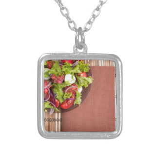 View from above on a plate with fresh salad silver plated necklace