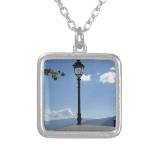 Vintage street lamp against blue sky silver plated necklace