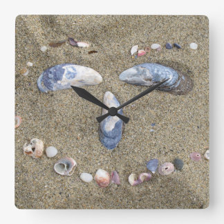 Wall clock face made in the sand with sea shells