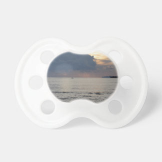 Warm sea sunset with cargo ship and a small boat baby pacifier
