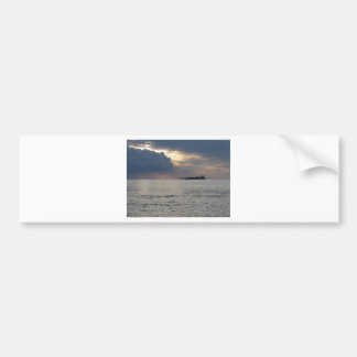 Warm sea sunset with cargo ship and a small boat bumper sticker