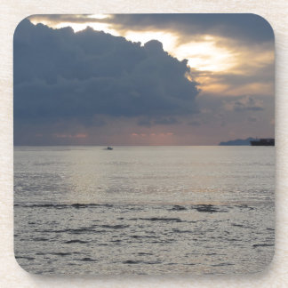 Warm sea sunset with cargo ship and a small boat drink coaster