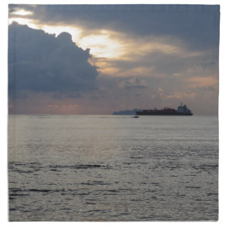 Warm sea sunset with cargo ship and a small boat napkin