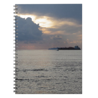 Warm sea sunset with cargo ship and a small boat notebook