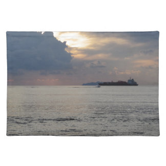 Warm sea sunset with cargo ship and a small boat placemat