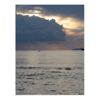 Warm sea sunset with cargo ship and a small boat postcard