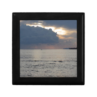 Warm sea sunset with cargo ship and a small boat small square gift box