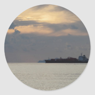 Warm sea sunset with cargo ship at the horizon classic round sticker