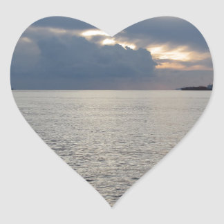 Warm sea sunset with cargo ship at the horizon heart sticker