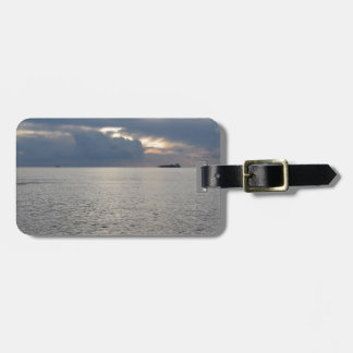 Warm sea sunset with cargo ship at the horizon luggage tag