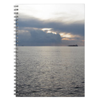 Warm sea sunset with cargo ship at the horizon notebooks