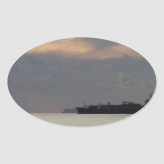 Warm sea sunset with cargo ship at the horizon oval sticker