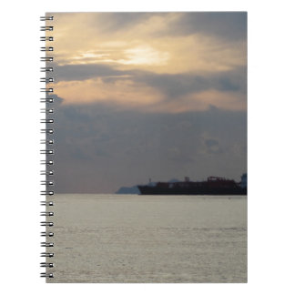 Warm sea sunset with cargo ship at the horizon spiral note book