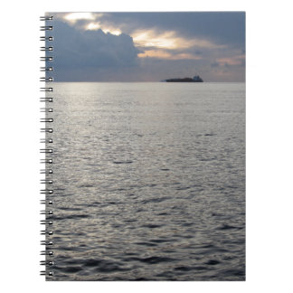 Warm sea sunset with cargo ship at the horizon spiral note books