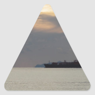 Warm sea sunset with cargo ship at the horizon triangle sticker
