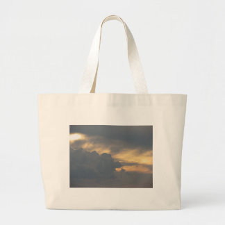Warm sky with giants cumulonimbus clouds at sunset large tote bag