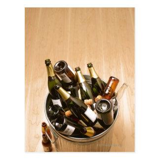 Waste bin full of empty champagne bottles on postcard