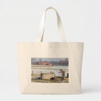 Water pump and well in winter snow landscape large tote bag