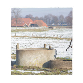Water pump and well in winter snow landscape notepad