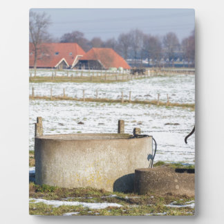 Water pump and well in winter snow landscape plaque