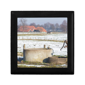 Water pump and well in winter snow landscape small square gift box