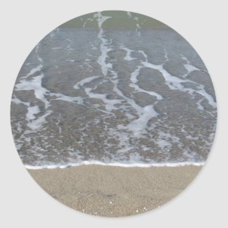 Wave of the sea on the sand beach classic round sticker