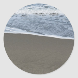 Wave of the sea on the sand beach round sticker