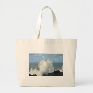 Waves breaking on a volcanic shore tote bags