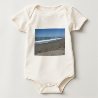 Waves of the sea on the sand beach baby bodysuit
