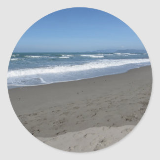 Waves of the sea on the sand beach classic round sticker