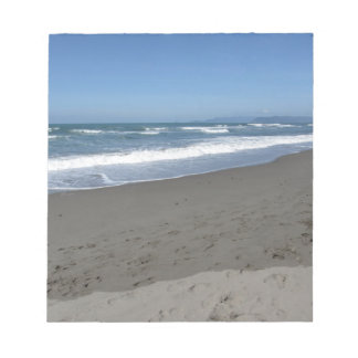 Waves of the sea on the sand beach notepad