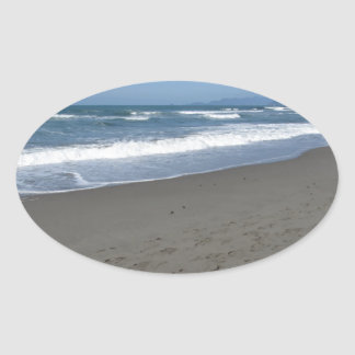 Waves of the sea on the sand beach oval sticker