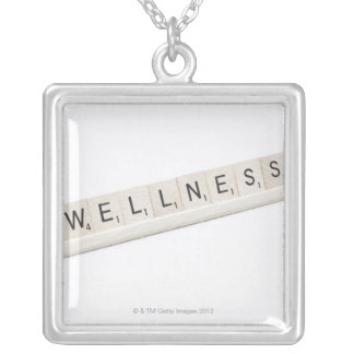 Wellness Spelled On A Word Board Game. Silver Plated Necklace