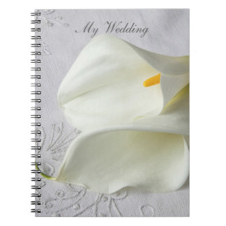 White calla lilies on linen wedding notebooks