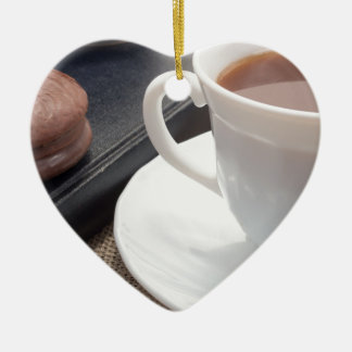 White cup of hot cocoa and a chocolate biscuit ceramic ornament