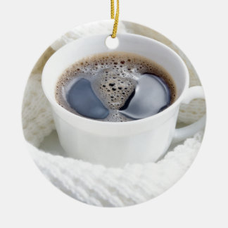 White cup of hot coffee surrounded by a white wool ceramic ornament