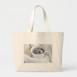 White cup of hot coffee surrounded by a white wool large tote bag