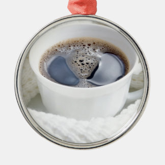 White cup of hot coffee surrounded by a white wool metal ornament