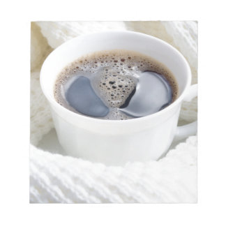 White cup of hot coffee surrounded by a white wool notepad
