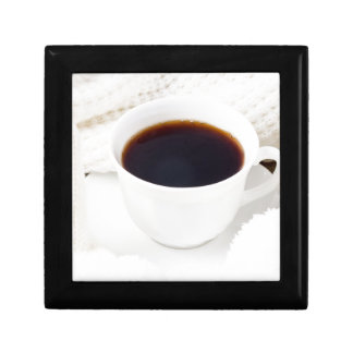 White cup with hot coffee and woolen mittens gift box