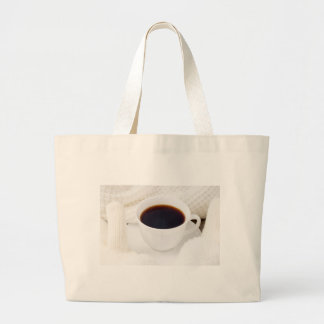 White cup with hot coffee and woolen mittens large tote bag