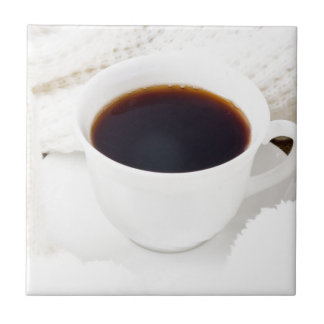 White cup with hot coffee and woolen mittens tile