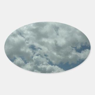White, fluffy clouds in blue sky oval sticker