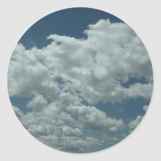 White, fluffy clouds in blue sky round sticker