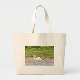 White mother swan swimming in line with cygnets large tote bag