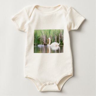 White mother swan swimming with chicks baby bodysuit