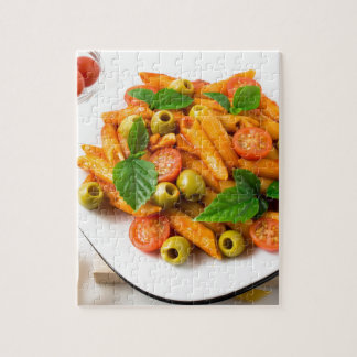 White plate of penne pasta decorated with cherry jigsaw puzzle