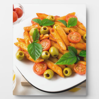 White plate of penne pasta decorated with cherry plaque