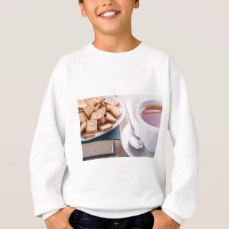 White plate with cookies on old book sweatshirt