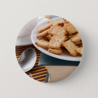 White plate with cookies on the old book 6 cm round badge